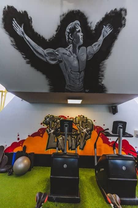 Trainingsgeräte und Arnold Schwarzenegger-Wandbild, Fitnessstudio Sams Gym